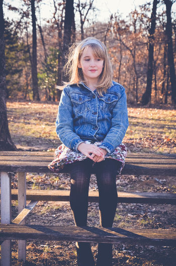 Girl sitting on picnic table at field