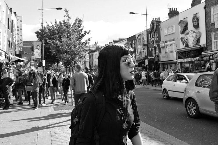 People standing on street in city against sky