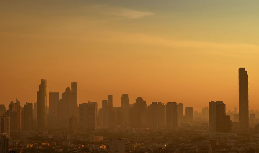 Air pollution. smog and fine dust of pm2.5 covered city in the morning with orange sunrise sky.