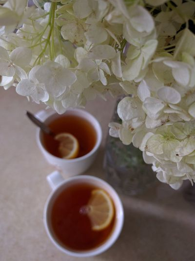 High angle view of coffee cups on table by flowers