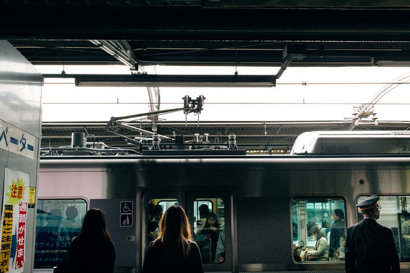 Rear view of people standing in train