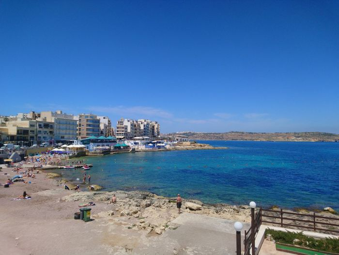 High angle view of sea and buildings against blue sky