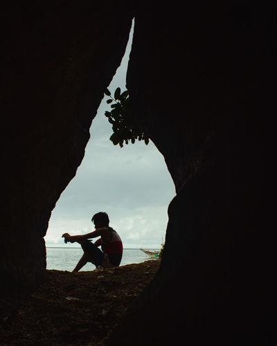 Silhouette man sitting on rock against sky