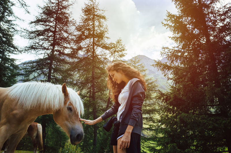 Woman touching horse while standing against trees