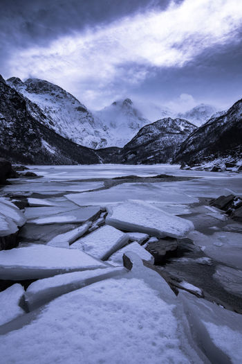 Scenic View Of Frozen Lake By Snowcapped Mountains Against Sky