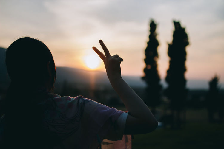 Rear view of silhouette woman showing peace sign against sky during sunset