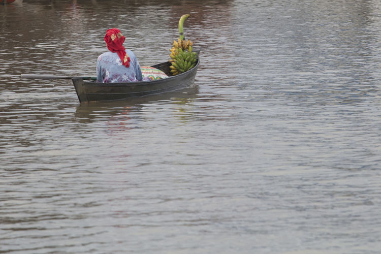 Rear view of person sitting in boat at lake