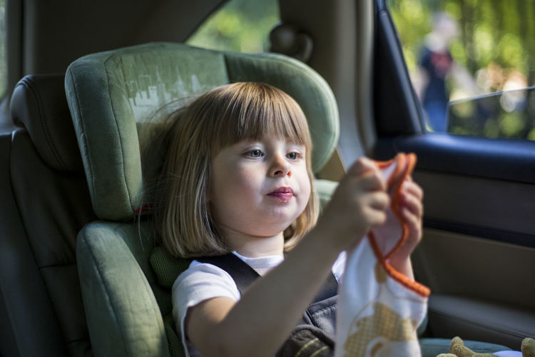 Close-up of girl sitting in car
