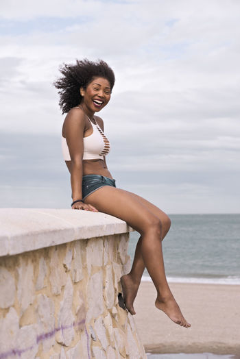 Portrait of smiling young woman on beach against sky