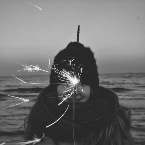 Girl Holding Sparkler Against Sea