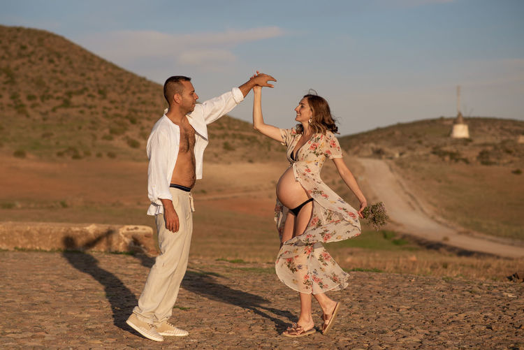 Pregnant woman with dancing man on footpath against sky