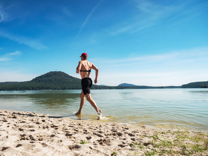 Shirtless fitness man exercise in training on the beach. muscular man is run in water along beach