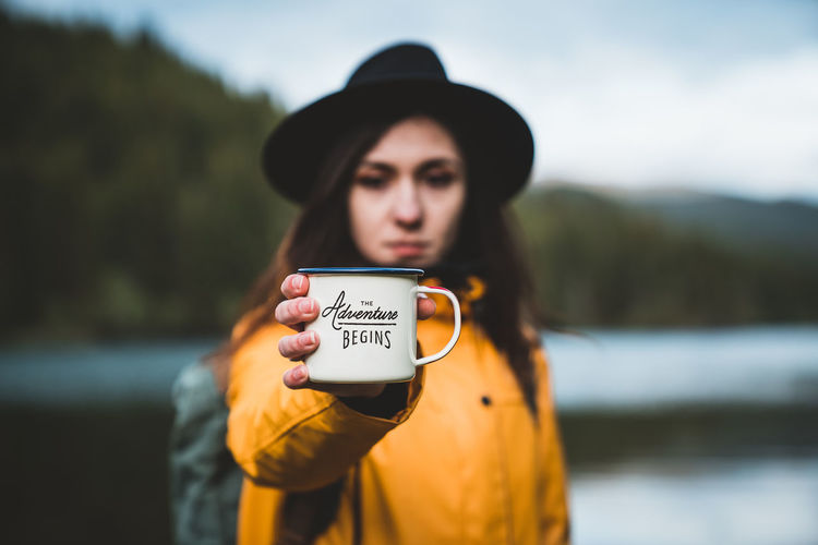 Portrait of young woman holding cup against lake