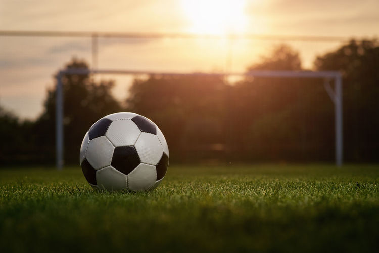 Surface level of soccer ball on field during sunset