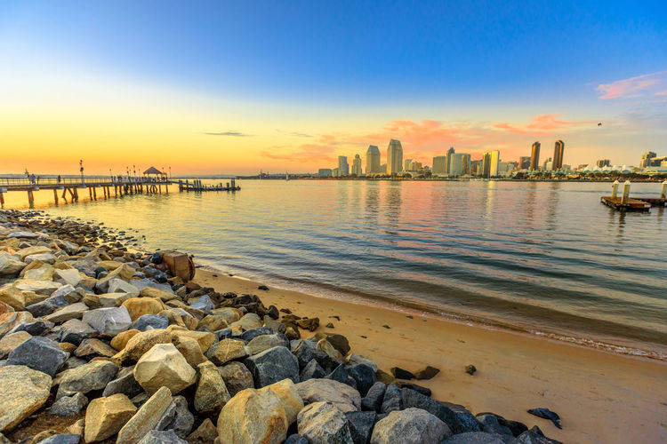 Scenic landscape with sunset colors sky of San Diego skyline with skyscrapers in San Diego Bay. Districts of Waterfront Marina skyline and urban downtown cityscape from Coronado Island. Coronado Coronado Beach Coronado Island Sea Beach San Diego California United States America American Skyline Seascape Cityscape Sun Dock Port Holiday Vacations Sunset Night Pier Water Sky Built Structure Architecture Rock Solid Building Exterior Nature Rock - Object Beauty In Nature Scenics - Nature No People Outdoors Reflection City Skyscraper Groyne