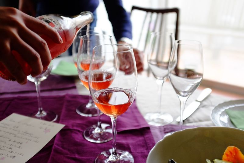 Cropped image of hand pouring wine in glass on table