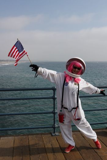 Portrait of mid adult woman in space suit standing on pier over sea against sky