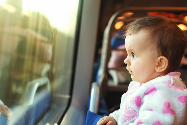 Cute baby girl looking though window in train