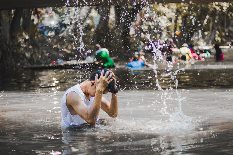 Man with head in hands amidst splashing water in lake