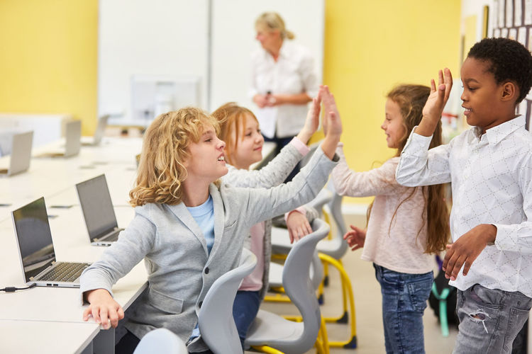 Cheerful school children giving high five at school