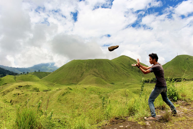 Side view of young man throwing rock while standing against cloudy sky