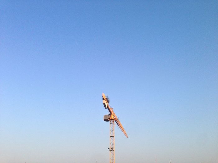 Low angle view of crane at construction site against clear sky