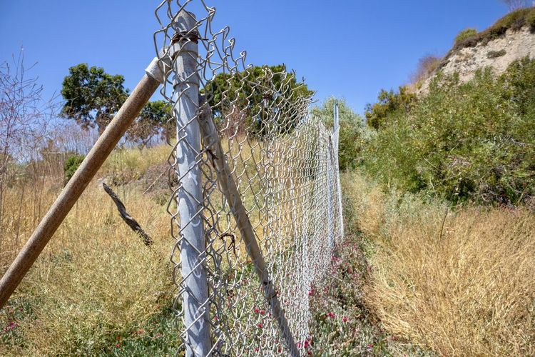chain link fence in a canyon against blue sky Plant Nature Land Tree Fence Sky Boundary Barrier Growth Field Day No People Safety Security Protection Clear Sky Wire Sunlight Landscape Beauty In Nature Outdoors Wooden Post Chain Link Fence Hiking