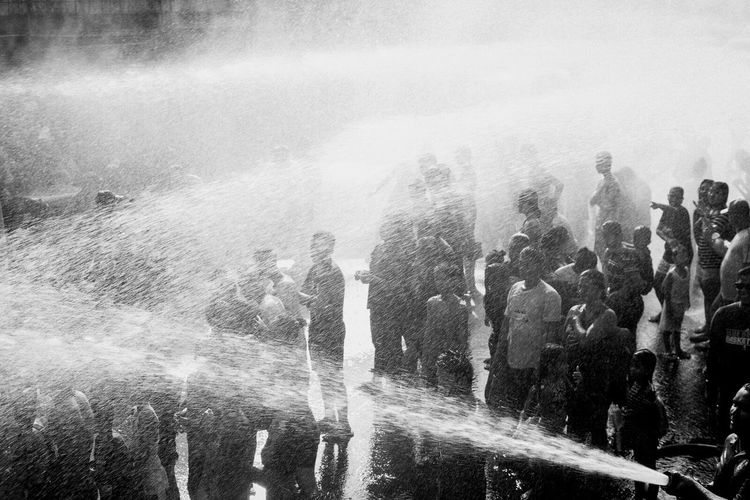 WHATTA! WHATTA! Fire hoses are used to spray water to residents of San Juan City in Metro Manila on 24 June 2017 as they celebrate Whatta Whatta Festival, an annual commemoration of the Feast of St. John The Baptist, who baptized Jesus Christ. The celebration is popularly done by splashing each other including passersby with water. On 2012, former City Mayor JV Ejercito changed the name of the festival from Feast of St. John the Baptist to Whatta Whatta. | The Photojournalist - 2017 EyeEm Awards Documentary Photography Untold Stories Everybodystreet EyeEm Best Shots The Human Condition EyeEmBestPics EyeEm Philippines 👍 Philippines Black And White Larrymonseratepiojo Rainy Days The Week On EyeEm Eyeemawards2017 Large Group Of People Lifestyles Crowd Wet Water People