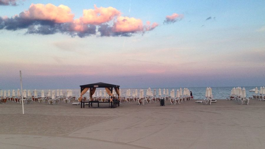 Gazebo With Lounge Chairs On Pier Against Sky During Sunset