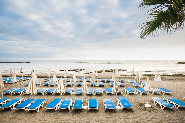 Empty seats at beach against cloudy sky