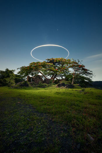 Low angle view of halo over field against sky