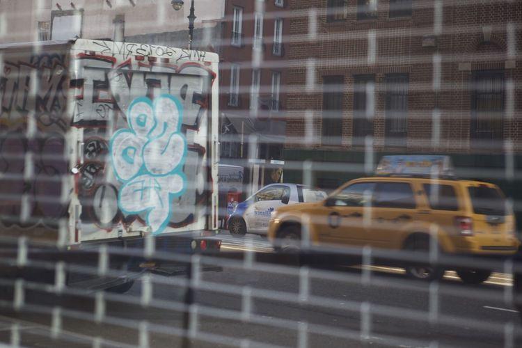 Cars on street seen through glass window
