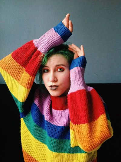 Portrait of young woman wearing colorful sweater at home