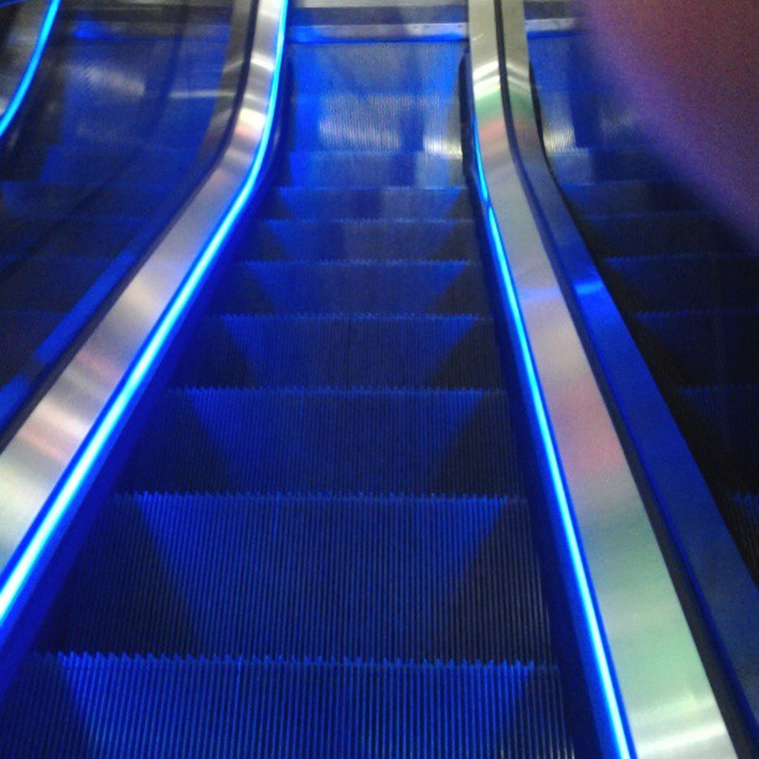 indoors, steps and staircases, steps, staircase, escalator, illuminated, railing, the way forward, empty, high angle view, modern, pattern, architecture, absence, diminishing perspective, built structure, ceiling, blue, no people, convenience