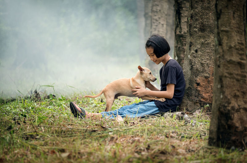 Side view of girl sitting with dog at forest