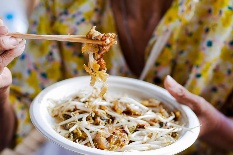 Close-up of hand holding noodles in bowl
