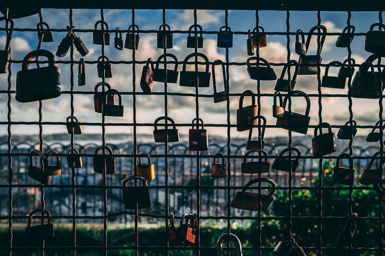 Close-up of padlocks hanging on chainlink fence