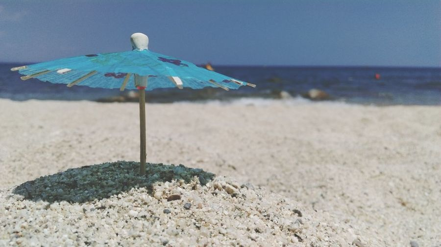 Close-up of drink umbrella on sand at beach against sky