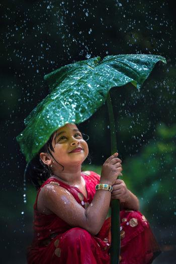 Portrait of smiling girl holding umbrella during rainy season
