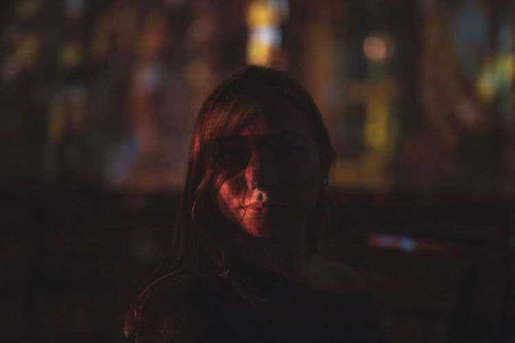 Close-up portrait of young woman standing outdoors at night