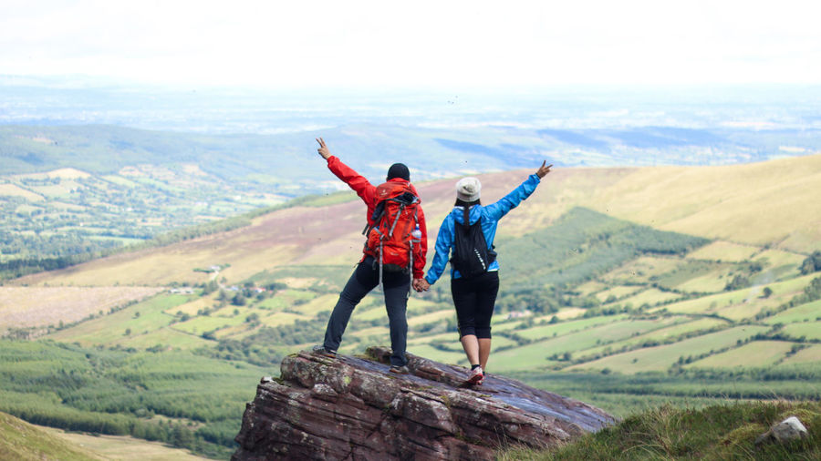 Couple gesturing peace sign on rock against landscape in sunny day