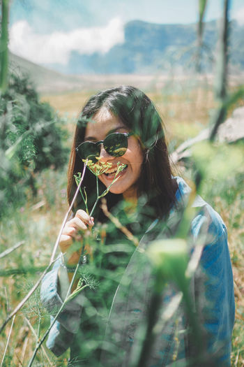 Portrait of young woman holding plant on field