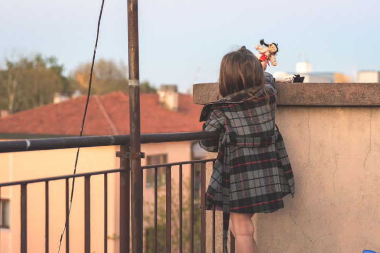 Rear view of girl playing with dolls on building terrace