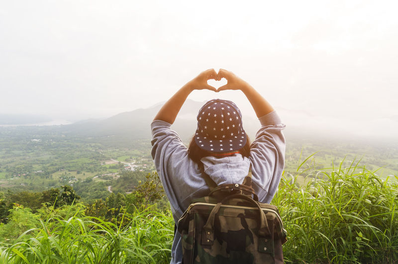 Rear View Of Woman Gesturing Heart Shape While Standing On Mountain Against Sky During Foggy Weather