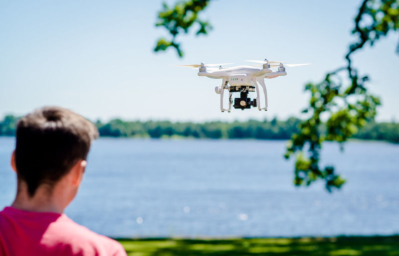 Quadrocopter with photo camera flying outdoors Camera Helicopter Man Quadcopter Quadrocopter Quadrotor Summertime Sunlight Camera - Photographic Equipment Day Flying Lake Lakeside One Person Outdoors Phantom Photography Photography Themes Rear View Robot Sky Start Summer Technology Unrecognizable Person