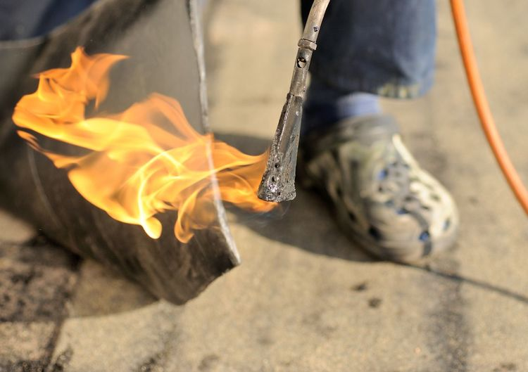 Man working with burner and insulation on the roof. InsulationWork Body Part Burner Burning Close-up Fire Fire - Natural Phenomenon Flame Glowing Heat - Temperature Human Body Part Human Leg Insulation Low Section Men One Person Outdoors Real People Shoe