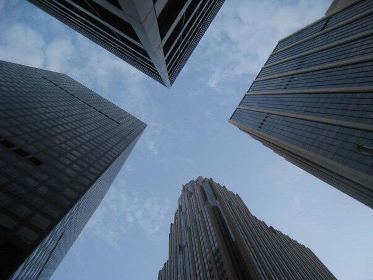 sky, low angle view, skyscraper, building exterior, tall - high, built structure, architecture, city, cloud - sky, directly below, office building exterior, outdoors, downtown district, modern, day, no people, corporate business, urban skyline, nature, office park, low