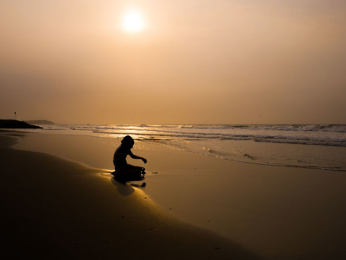 Silhouette boy sitting on sand at beach against sky during sunset