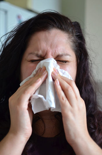Woman blowing her nose hard into a tissue at home At Home Casual Clothing Close-up Coughing Covering Facial Expression Female Front View Headshot Health Holding Home Indoors  Long Hair Person Sneeze Sneezing Sunglassess  Tissue Woman Young Adult