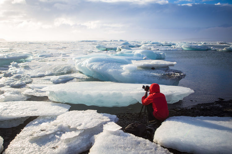 Person photographing amidst glaciers on jokulsarlon lake